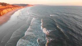 Κύματα στην παραλία στο ηλιοβασίλεμα