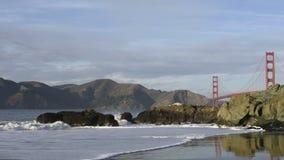 Κύματα στην παραλία Baker με τη χρυσή γέφυρα πυλών στο υπόβαθρο φιλμ μικρού μήκους