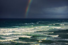 Κύματα στην τραχιά θάλασσα με τα θυελλώδη σύννεφα και το ουράνιο τόξο Στοκ φωτογραφία με δικαίωμα ελεύθερης χρήσης