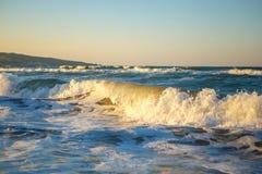 Κύματα στο ηλιοβασίλεμα όμορφη θάλασσα με τα κύματα και τον ψεκασμό, η έννοια του ταξιδιού, μια όμορφη κάρτα παραλιών Στοκ Εικόνα