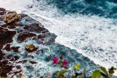 Κύματα του Ειρηνικού Ωκεανού μέσω των λουλουδιών Bougainvillea Uluwatu, Μπαλί, Ινδονησία Στοκ εικόνα με δικαίωμα ελεύθερης χρήσης