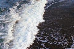 Κύμα θάλασσας με τον άσπρο αφρό στη σκοτεινή άμμο Στοκ φωτογραφία με δικαίωμα ελεύθερης χρήσης