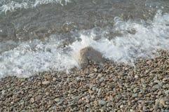 Κύμα θάλασσας στην ακτή μιας παραλίας χαλικιών, νερό, αφρός, υπόβαθρο Στοκ εικόνες με δικαίωμα ελεύθερης χρήσης