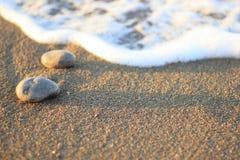 Κύμα θάλασσας στην άμμο και πέτρα στην ανατολή Στοκ Εικόνα