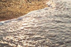 Κύμα θάλασσας στην άμμο και πέτρα στην ανατολή Στοκ Εικόνες