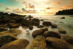 Κύμα θάλασσας στο βράχο στο ηλιοβασίλεμα Στοκ Εικόνες
