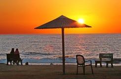 Κύμα πάγκων καρεκλών ομπρελών παραλιών θάλασσας ήλιων ηλιοβασιλέματος στοκ φωτογραφίες με δικαίωμα ελεύθερης χρήσης