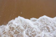 Κύμα της θάλασσας με τον άσπρο αφρό στα πλαίσια μιας αμμώδους παραλίας Στοκ Εικόνα