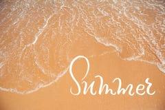 Κύμα της θάλασσας στο καλοκαίρι παραλιών και λέξης άμμου Εγγραφή καλλιγραφίας Στοκ Φωτογραφίες