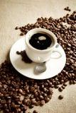 Κύμα φιαγμένο από φασόλια καφέ με το φλυτζάνι του frothy καφέ Στοκ Φωτογραφίες