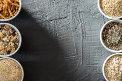 Κύπελλα με ολόκληρους τους υδατάνθρακες σιταριού, τις βρώμες, το καφετί ρύζι, τους σπόρους, quinoa και ολόκληρα τα ζυμαρικά σιταρ Στοκ Εικόνες