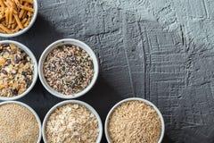 Κύπελλα με ολόκληρους τους υδατάνθρακες σιταριού, τις βρώμες, το καφετί ρύζι, τους σπόρους, quinoa και ολόκληρα τα ζυμαρικά σιταρ Στοκ Εικόνα