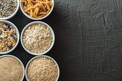 Κύπελλα με ολόκληρους τους υδατάνθρακες σιταριού, τις βρώμες, το καφετί ρύζι, τους σπόρους, quinoa και ολόκληρα τα ζυμαρικά σιταρ Στοκ Φωτογραφίες