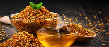 Κύπελλα με τη γύρη και το μέλι μελισσών στον πίνακα κουζινών Στοκ Εικόνα
