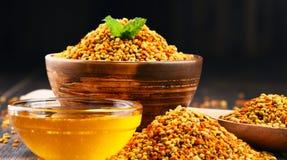 Κύπελλα με τη γύρη και το μέλι μελισσών στον πίνακα κουζινών Στοκ Εικόνες
