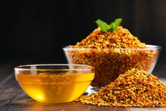 Κύπελλα με τη γύρη και το μέλι μελισσών στον πίνακα κουζινών Στοκ Φωτογραφία