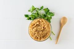 Κύπελλο βρασμένο quinoa που διακοσμείται με το μαϊντανό σε έναν άσπρο πίνακα κορυφαία όψη Επίπεδος βάλτε στοκ φωτογραφία