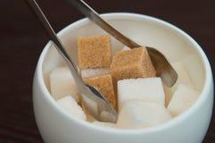 Κύπελλο ζάχαρης με τους κύβους της άσπρων ζάχαρης καλάμων και των ζάχαρη-λαβίδων Επιτραπέζιοι διορισμοί στον καφέ πόλεων Στοκ Φωτογραφία