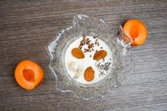 Κύπελλο με το γιαούρτι και τους διαφορετικούς σπόρους, το αμύγδαλο και το βερίκοκο Στοκ Φωτογραφία
