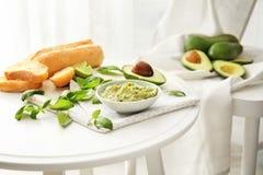 Κύπελλο με το νόστιμους guacamole, το βασιλικό και το ψωμί στον πίνακα στοκ εικόνα με δικαίωμα ελεύθερης χρήσης