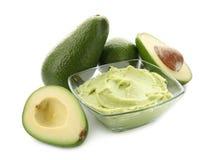 Κύπελλο με το νόστιμο guacamole και ώριμα αβοκάντο στο άσπρο υπόβαθρο στοκ εικόνες