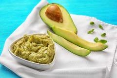 Κύπελλο με το νόστιμο guacamole και ώριμο αβοκάντο στον πίνακα στοκ εικόνες
