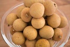 Κύπελλο που γεμίζουν με φρούτα Dimocarpus Longan σωρών στοκ φωτογραφίες