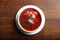 Κύπελλο της κόκκινης σούπας παντζαριών στο άσπρο πιάτο Στοκ εικόνα με δικαίωμα ελεύθερης χρήσης