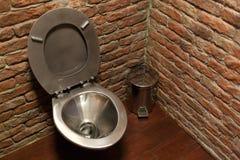 Κύπελλο τουαλετών ανοξείδωτου στο υπόβαθρο τουβλότοιχος Στοκ φωτογραφία με δικαίωμα ελεύθερης χρήσης