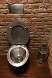 Κύπελλο τουαλετών ανοξείδωτου στο υπόβαθρο τουβλότοιχος Στοκ Εικόνες