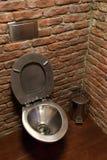 Κύπελλο τουαλετών ανοξείδωτου στο υπόβαθρο τουβλότοιχος Στοκ Εικόνα