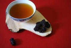 Κύπελλο του κινεζικού τσαγιού χορταριών με jujubes στο κόκκινο υπόβαθρο Στοκ φωτογραφία με δικαίωμα ελεύθερης χρήσης