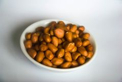 Κύπελλο των οργανικών φυστικιών στο κεραμικό άσπρο πιάτο Στοκ Φωτογραφία