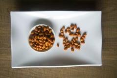 Κύπελλο των οργανικών φυστικιών στο κεραμικό άσπρο πιάτο Στοκ Εικόνες