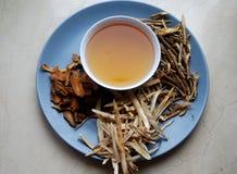 Κύπελλο των παρασκευασμένων κινεζικών χορταριών με τις ξηρές ανάμεικτες ρίζες κατά μέρος Στοκ Φωτογραφίες
