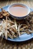 Κύπελλο των παρασκευασμένων κινεζικών χορταριών με τις ξηρές ανάμεικτες ρίζες κατά μέρος Στοκ εικόνα με δικαίωμα ελεύθερης χρήσης