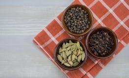 Κύπελλα των γαρίφαλων καρδάμωμων και των δημητριακών πιπεριών στοκ φωτογραφία με δικαίωμα ελεύθερης χρήσης