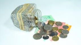 Κύπελλο γυαλιού με τους σωρούς των νομισμάτων και των τραπεζογραμματίων της Μαλαισίας Στοκ εικόνες με δικαίωμα ελεύθερης χρήσης