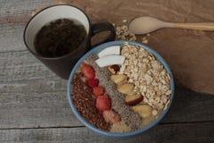 Κύπελλο καταφερτζήδων μούρων προγευμάτων που ολοκληρώνεται με τα σμέουρα, Chia, σπόροι λιναριού, καρύδα, καρύδι Στοκ Φωτογραφίες