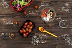 Κύπελλο με την ελληνική σαλάτα που στέκεται κοντά στις ντομάτες Στοκ Εικόνες