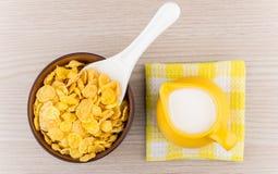 Κύπελλο με τις νιφάδες καλαμποκιού και την κανάτα του γάλακτος στην πετσέτα Στοκ εικόνα με δικαίωμα ελεύθερης χρήσης