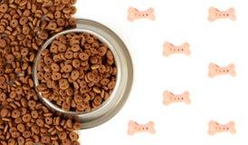 Κύπελλο σκυλιών με την τροφή κατοικίδιων ζώων με το μισό άσπρο υπόβαθρο και τα διεσπαρμένα ξηρά τρόφιμα στοκ εικόνες