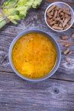 Κύπελλο σούπας του αποθέματος κοτόπουλου με τα νουντλς, τα καρότα και το φρέσκο κρεμμύδι Στοκ Εικόνα