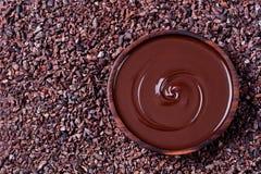 Κύπελλο της λειωμένης σοκολάτας και του ξύλινου κουταλιού φασόλια ενός στα συντριμμένα ακατέργαστα κακάου, nibs διαστημική τοπ άπ Στοκ Εικόνες
