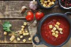 Κύπελλο της σούπας ντοματών με τις κροτίδες και το γαρίφαλο στο εκλεκτής ποιότητας ύφασμα και του αγροτικού ξύλινου υποβάθρου, το Στοκ Εικόνες