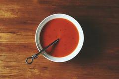 Κύπελλο της σούπας ντοματών στο δρύινο πίνακα με τις σκιές Στοκ Φωτογραφίες