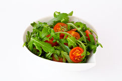 Κύπελλο του φρέσκων πράσινων, φυσικών arugula και των ντοματών κερασιών Στοκ εικόνες με δικαίωμα ελεύθερης χρήσης