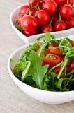 Κύπελλο του φρέσκων πράσινων, φυσικών arugula και των ντοματών κερασιών Στοκ Φωτογραφία