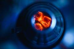 Κύπελλο του hookah με τους καυτούς κόκκινους άνθρακες για το κάπνισμα και τη χαλάρωση σε ένα μπλε υπόβαθρο Στοκ Φωτογραφία