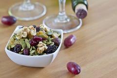 Κύπελλο των σπόρων καρυδιών με το θολωμένα μπουκάλι και το γυαλί κρασιού στο υπόβαθρο Στοκ φωτογραφία με δικαίωμα ελεύθερης χρήσης